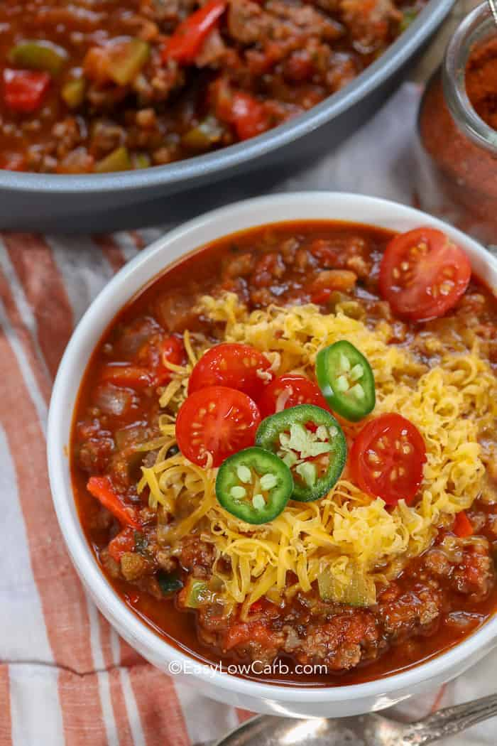 A while bowl full of keto chili topped with fresh cheddar cheese, tomatoes, and jalapenos.