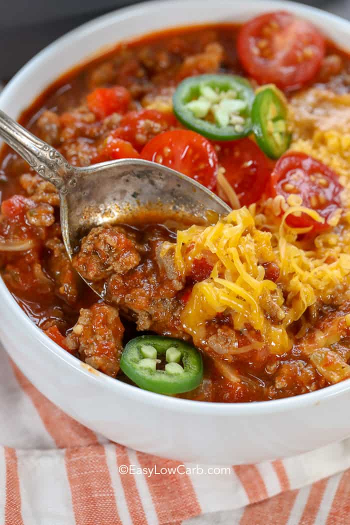 A spoon full of chili garnished with tomatoes, cheese, and jalapenos.
