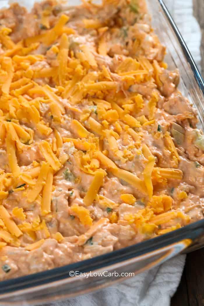 Creamy low carb buffalo chicken dip in a clear casserole dish before baking.