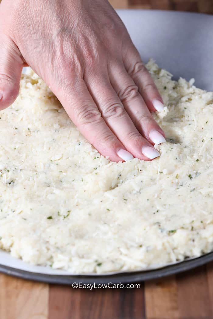 Cauliflower Pizza Crust as it is pressed onto a pizza pan