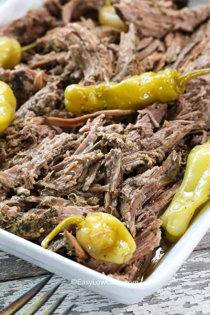 Mississippi pot roast pulled in a white casserole dish topped with pepperoncini.