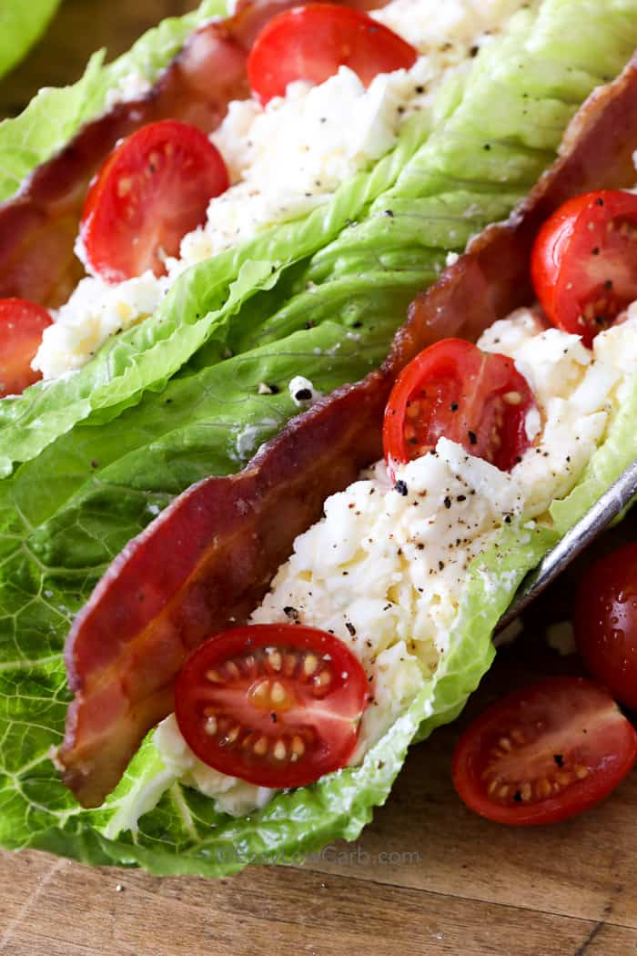 close up photo of lettuce leaves filled with tomatoes, bacon and egg salad