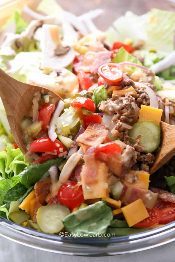 A close up of bacon cheeseburger salad filled with tomatoes, pickles, ground beef, cheese, and bacon.