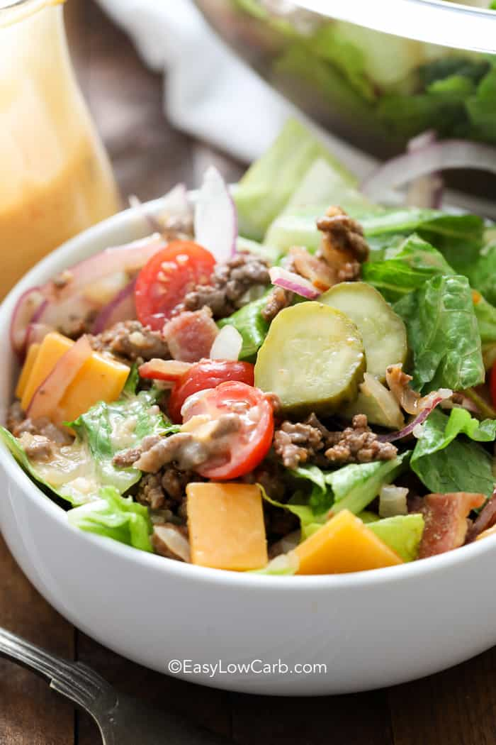 A white bowl of Bacon Cheeseburger Salad topped with pickles, tomatoes, and cheese.