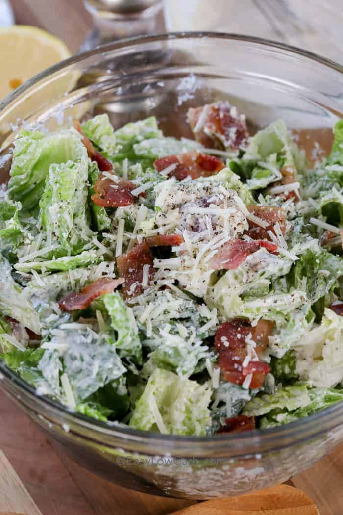 A bowl of fresh keto caesar salad topped with crumbled bacon and parmesan cheese