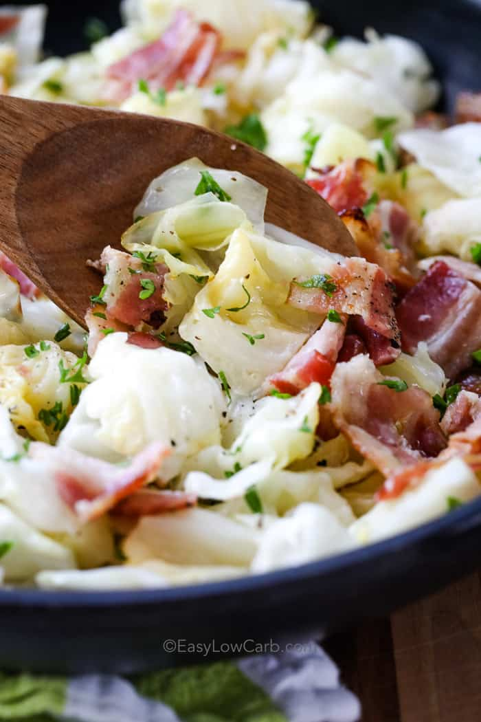 Fried cabbage with bacon being scooped with a wooden spoon.
