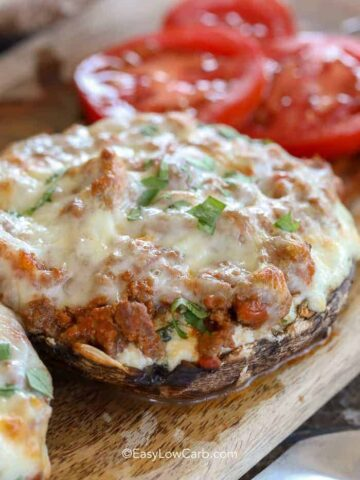 Lasagna Stuffed Mushrooms on a wood board with tomatoes in the background