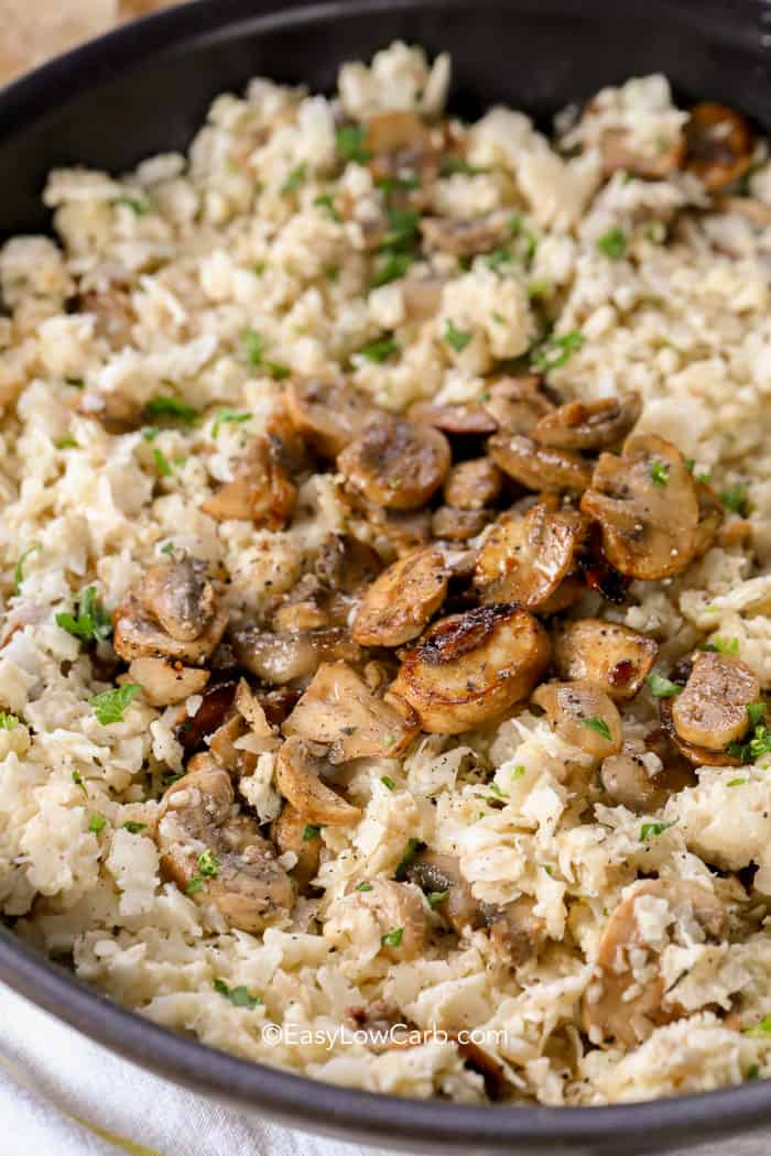 closeup of Cauliflower Mushroom Risotto in a skillet topped with mushrooms and parsley