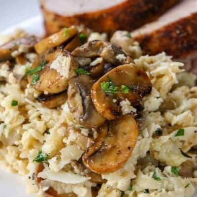 Cauliflower Mushroom Risotto in a skillet with mushrooms and parsley served on a plate with meat