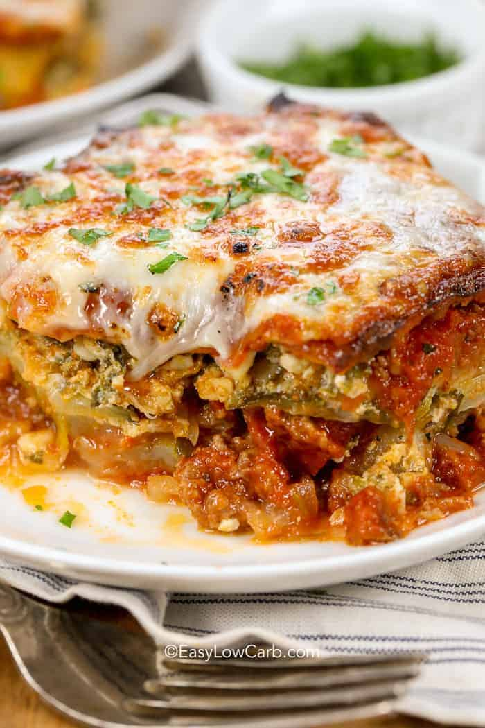 Zucchini lasagna garnished with parsley on a white plate, with a bite taken out of it, and a fork on the side