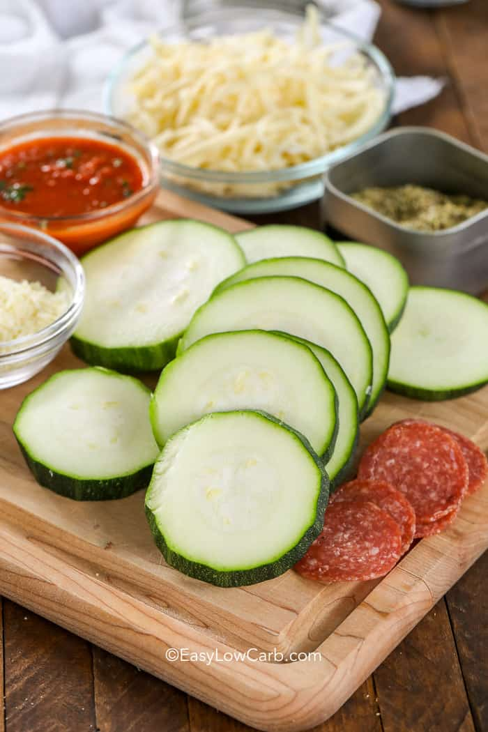 Zucchini slices and other ingredients for Zucchini Pizza bites arranged on a wooden cutting board.