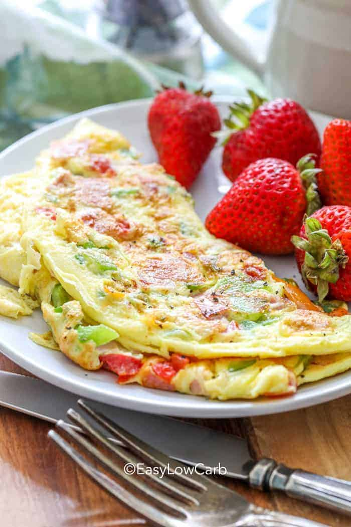 Denver omelet on a plate with strawberries.