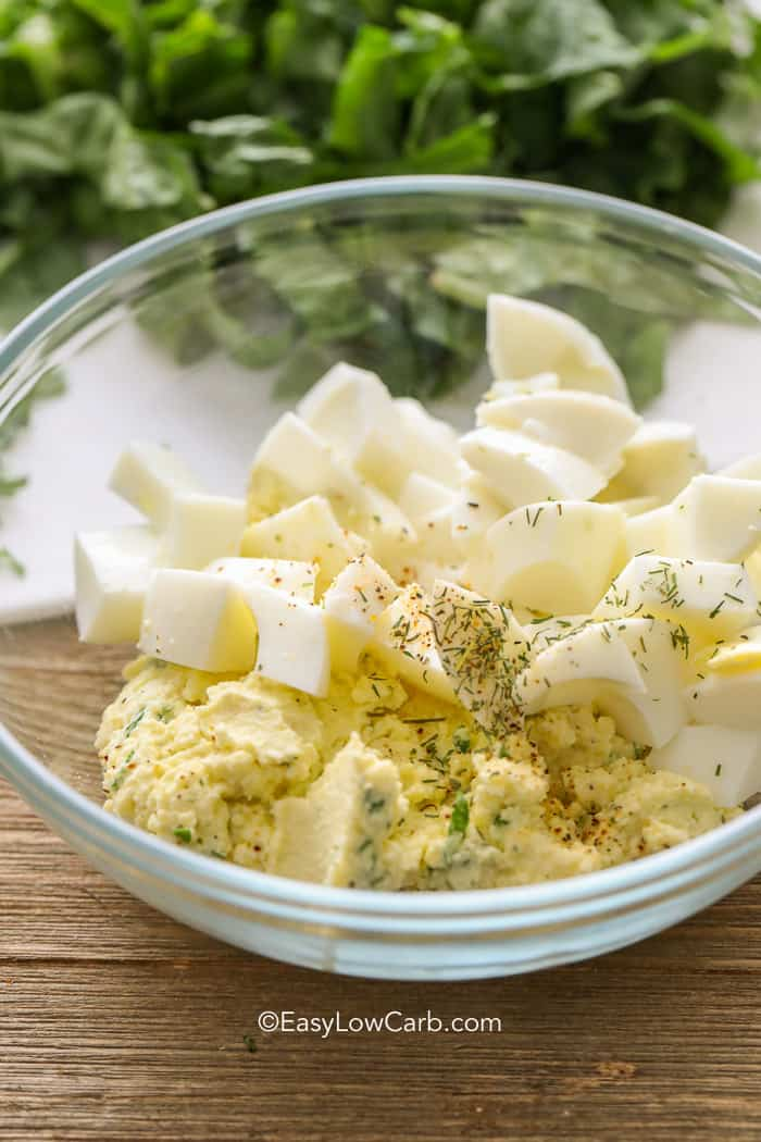 Keto egg salad ingredients in a clear mixing bowl with greens in the background.