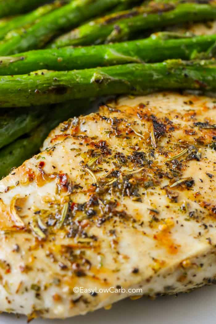 Oven roasted chicken breast on a plate next to asparagus.