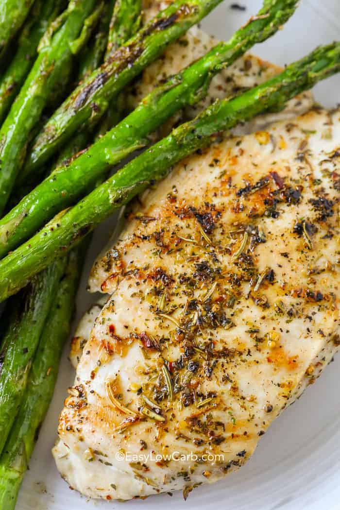 Juicy roasted chicken breast on a plate with asparagus.