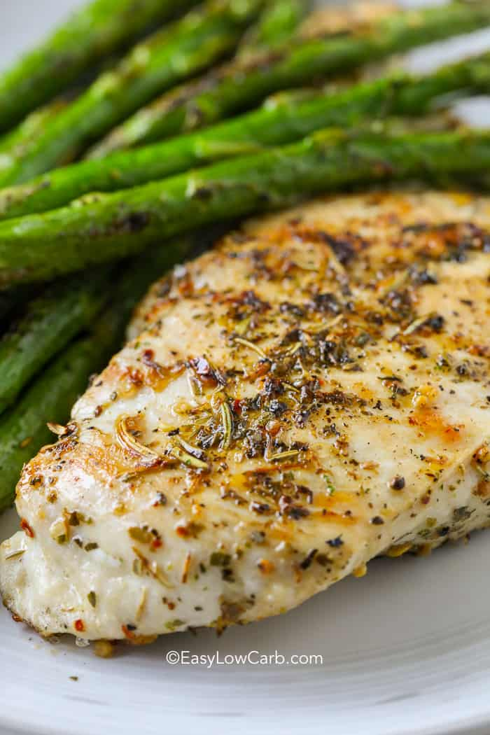 Perfect roasted chicken breast on a bed of asparagus on a white plate.