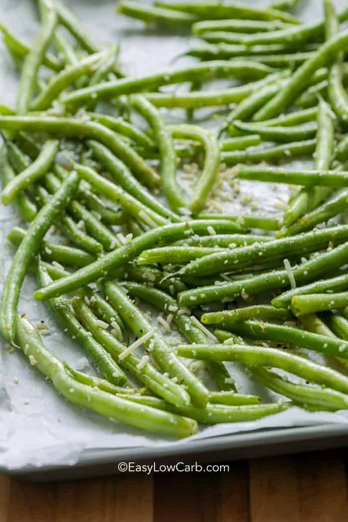 Roasted green beans on a baking sheet toped with parmesan, garlic, salt, and pepper.