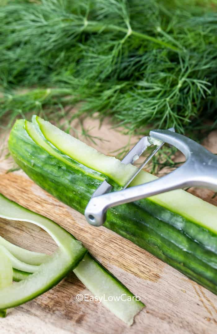 English cucumbers being sliced with a vegetable peeler.