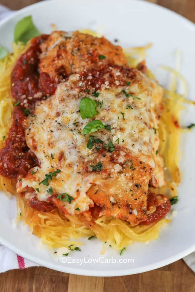 Low Carb Chicken Parmesan on spaghetti squash on a white plate