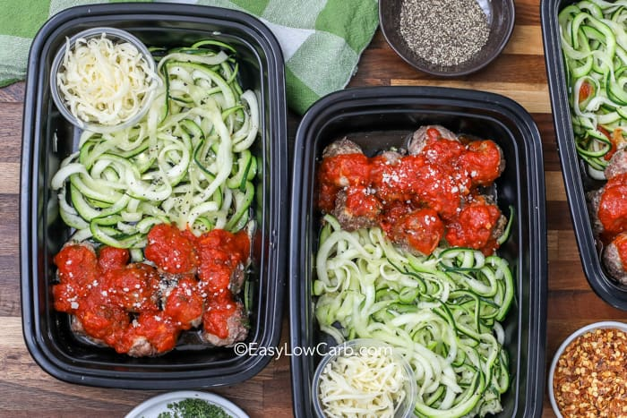Overview of two containers filled with easy low carb spaghetti and meatballs, served with a side of parmesan cheese and chili flakes.