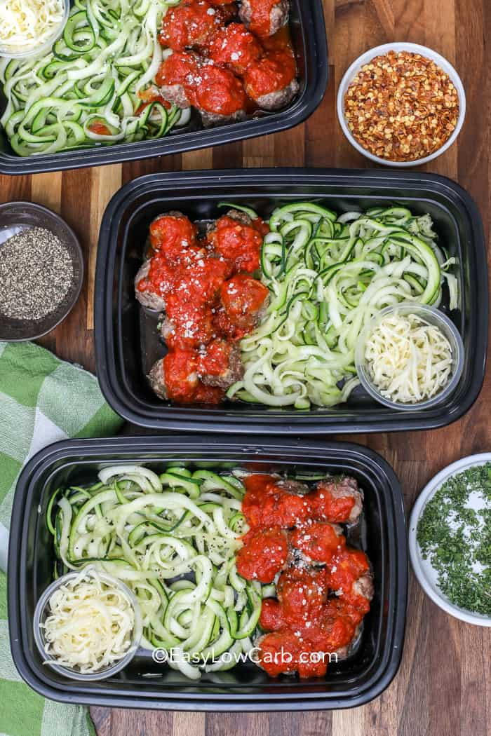 Overview of three containers with zoodles, meatballs and pasta sauce. Served with a side of parmesan cheese and chili flakes. Garnished with black pepper and parsley.