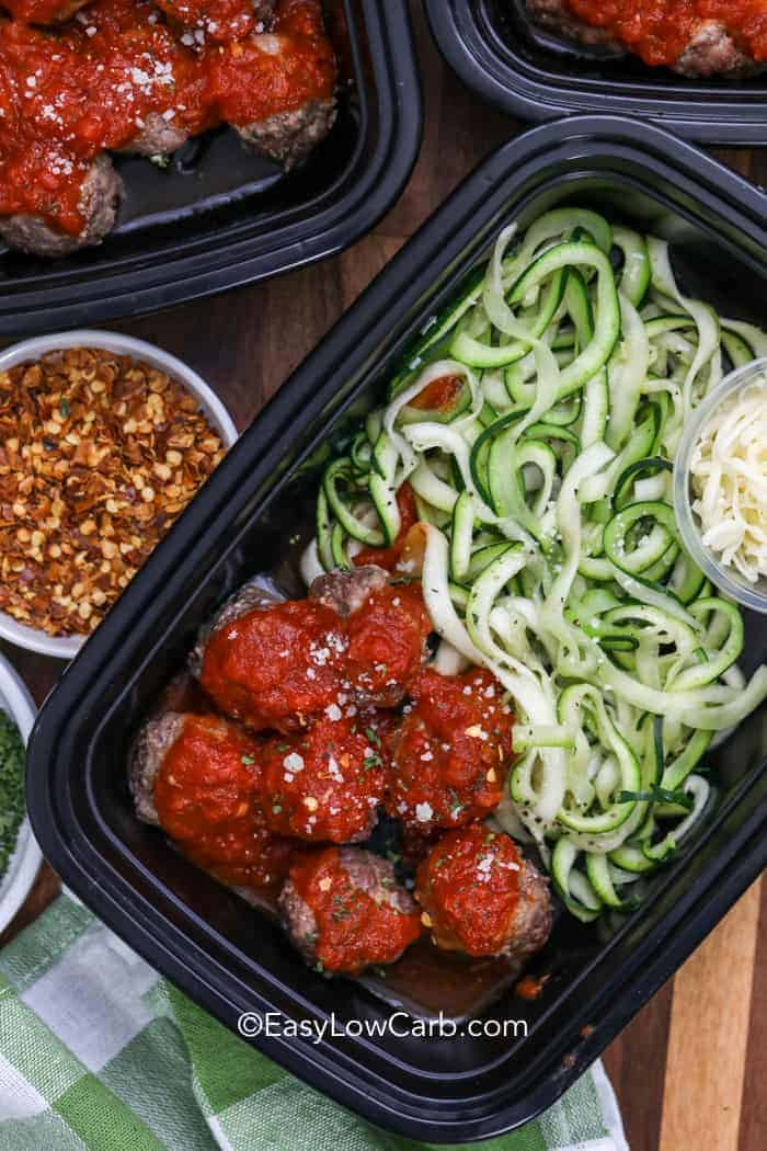 A container with easy low carb spaghetti and meatballs. Served with a side of parmesan cheese and chili flakes.
