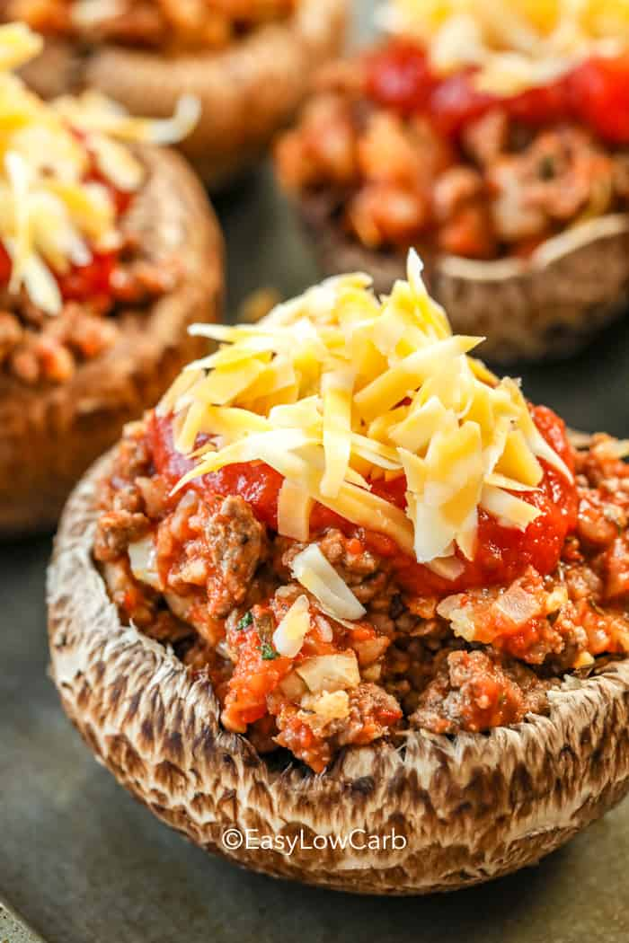 Portobello mushrooms stuffed with meat sauce and topped with shredded cheese.