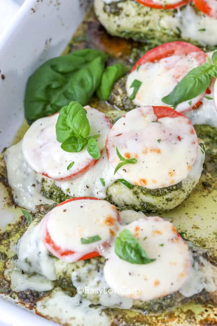 Pesto Chicken topped with sliced tomatoes and mozzarella on a baking pan. Garnished with basil.