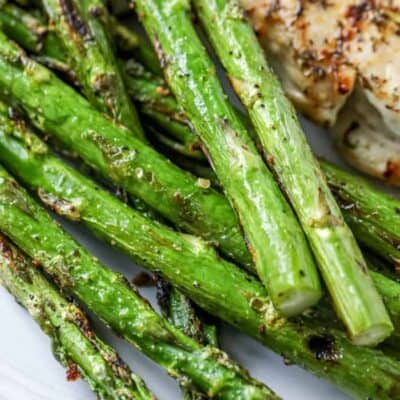 closeup of roasted asparagus on a white plate