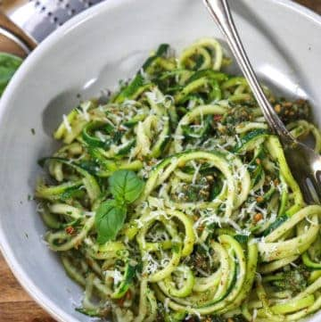 overhead of Zucchini Almond Pesto garnished with basil in a white dish