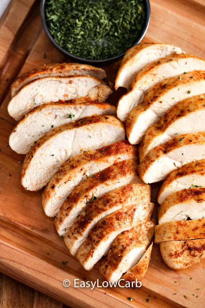 Two cooked chicken breasts sliced and laying on a wooden board.