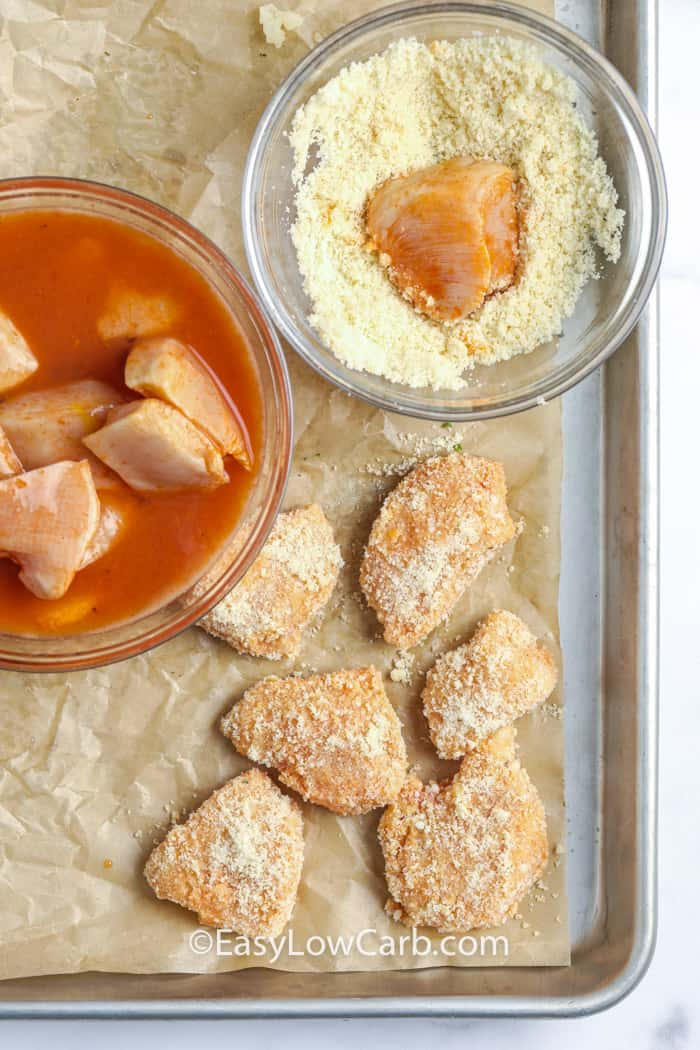 Chicken marinated in a bowl of buffalo sauce, then dipped in a bowl of coating and placed on a lined baking sheet.