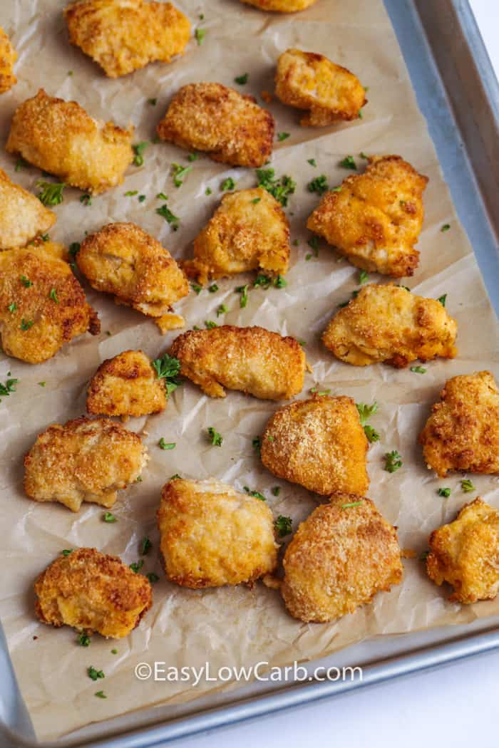 baked buffalo chicken bites with fresh chopped parsley on a parchment lined baking sheet