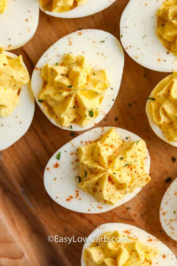 Keto Deviled Eggs on a wooden board garnished with paprika and fresh parsley