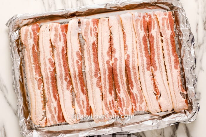 Bacon slices laid out on a baking sheet prior to being cooked.