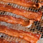 Cooked bacon slices laid out on a rack