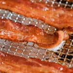 Oven fried bacon slices laid out on a rack with title