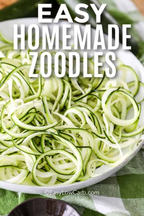 Zoodles in a white dish with zucchini in the background with a title