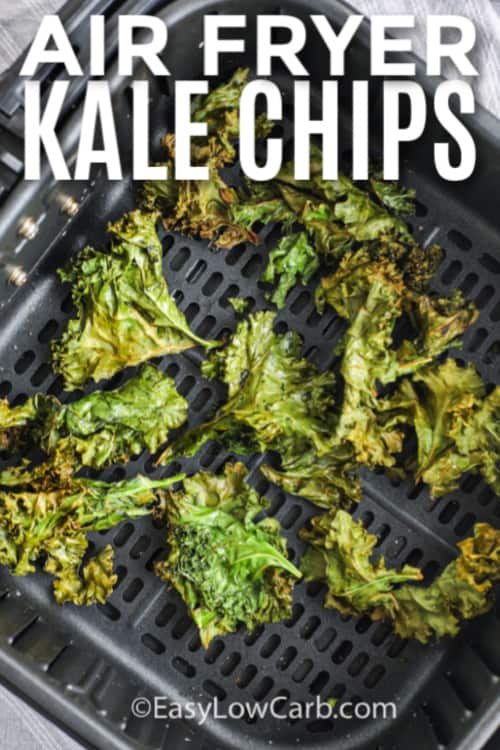 Prepared kale chips in the bottom of an air fryer with writing.