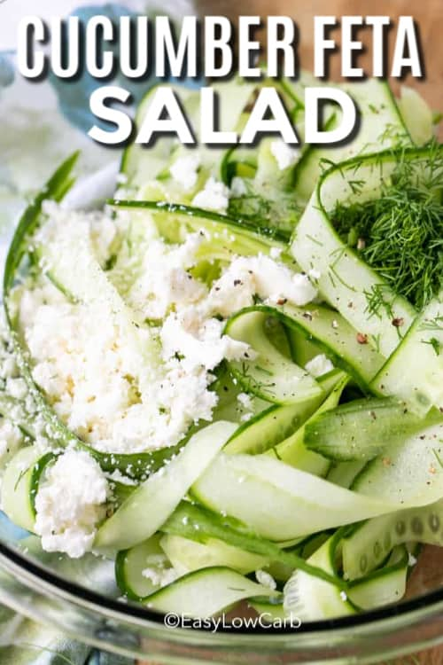 Cucumber feta salad in a clear bowl with a title.
