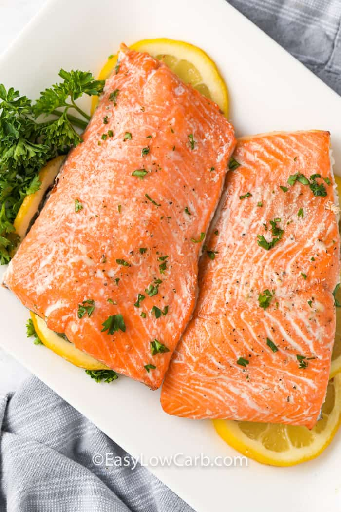 Salmon in the air fryer on a white plate with garnish and lemons