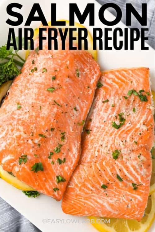 Salmon in the air fryer on a white plate with garnish and lemons, with a title.