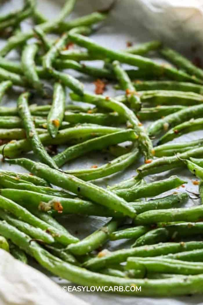 Green Beans roasted on a parchment lined baking sheet.