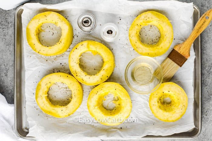 spreading oil on squash to show How to Cook Spaghetti Squash