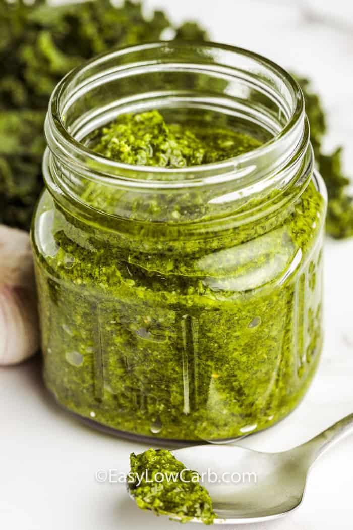 Kale Pesto in a jar with ingredients surrounding it