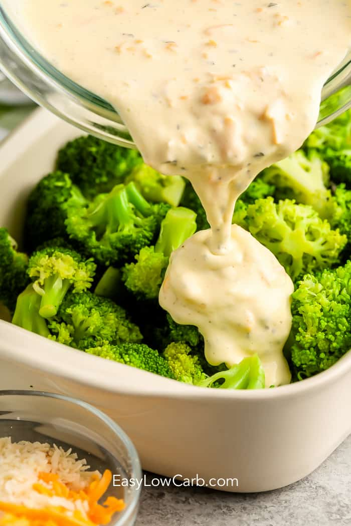 Pouring cheese sauce over broccoli for the best broccoli casserole
