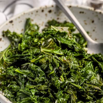 sauteed kale and garlic in a bowl with a spoon.