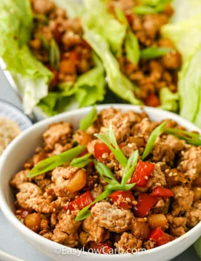 close up of filling for Easy Chicken Lettuce Wraps with lettuce wraps in the back