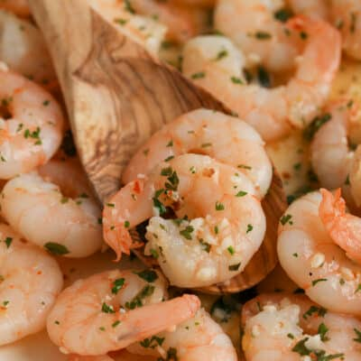 close up of wooden spoon scooping butter garlic shrimp