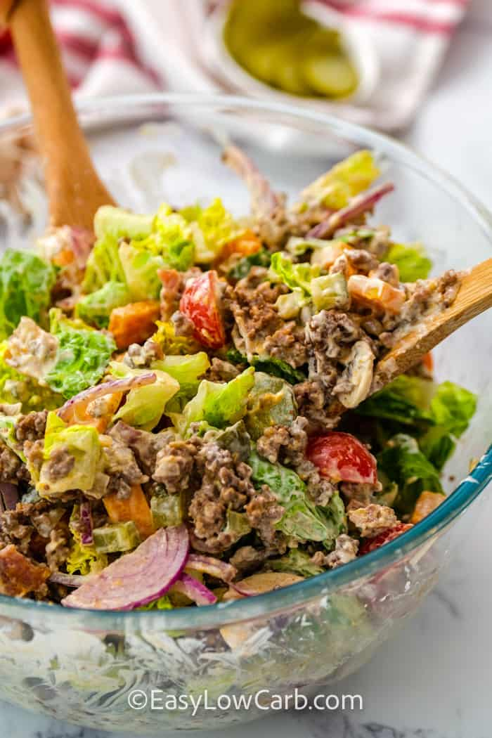 mixed Cheeseburger Salad in a serving bowl with wooden spoons